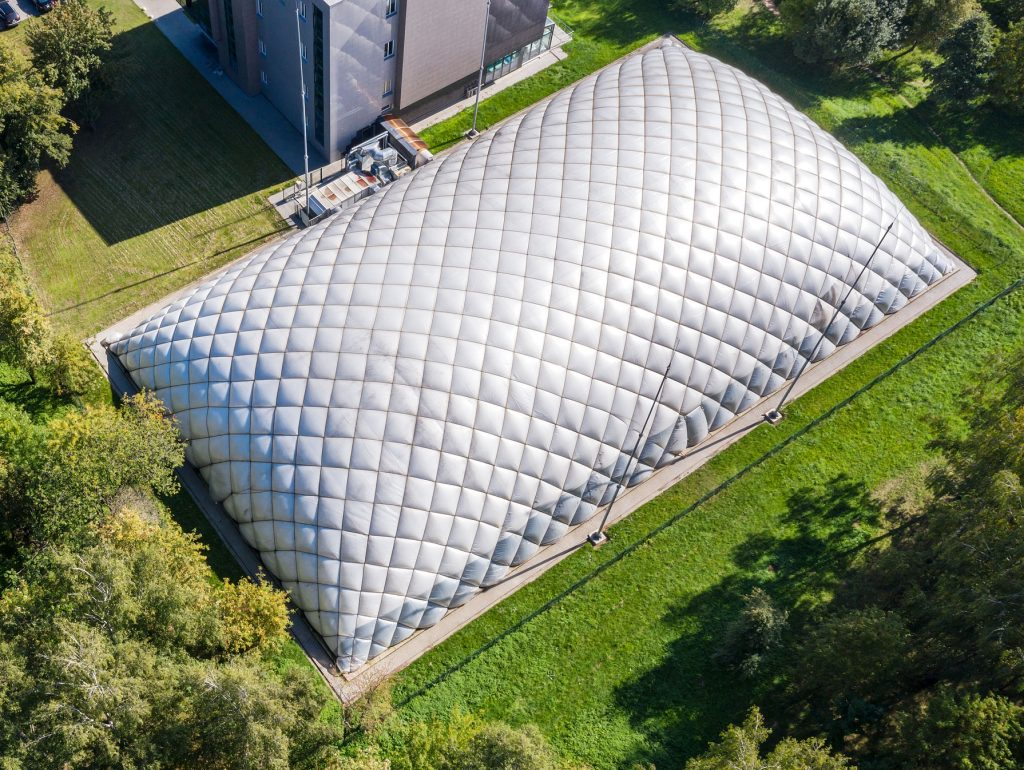 dome of inflatable tennis court in park in summer. aerial view of sports centre